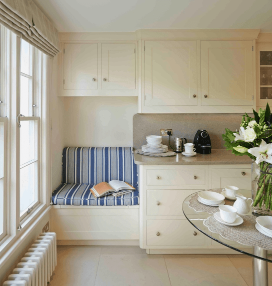 Classic white kitchen boasting a reading nook in the corner fitted with an upholstered bench seat that's surrounded by wooden cabinetry and drawers.
