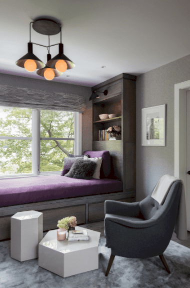 Black pendant lights illuminate this reading nook that showcases a gray armchair and sleek hexagonal coffee tables. It has a window seat topped with purple cushion and fluffy pillows.