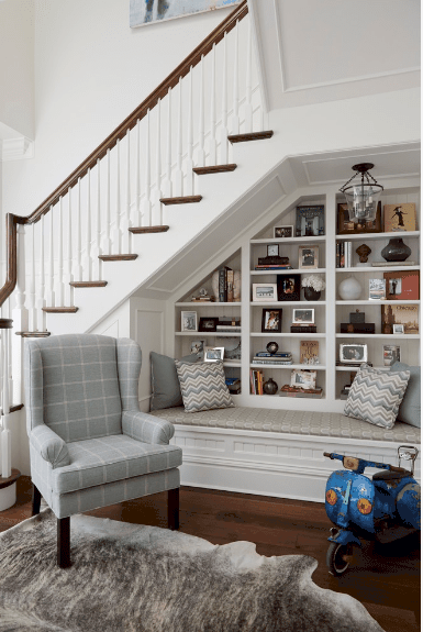 Traditional foyer features a reading nook underneath the staircase. It has a checkered wingback chair that sits in front of the built-in bench with open shelving filled with books and decors.