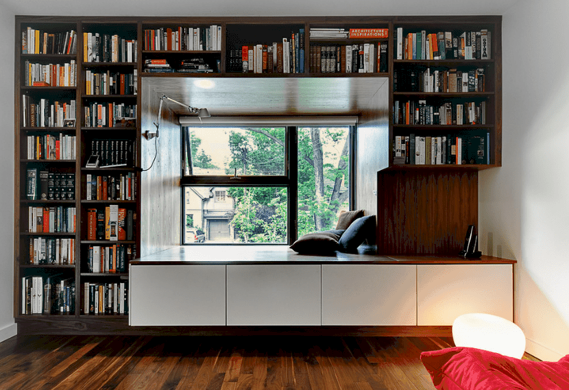This reading nook offers dark wood bookshelves contrasted by white drawers. It is illuminated by a wall sconce and natural light from the glazed windows.