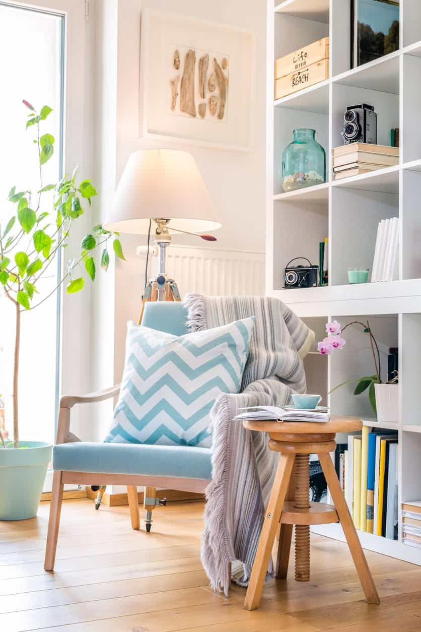 White reading nook features a wooden chair accented with blue chevron pillow and striped throw blanket. It is paired with a round side table and tripod floor lamp.