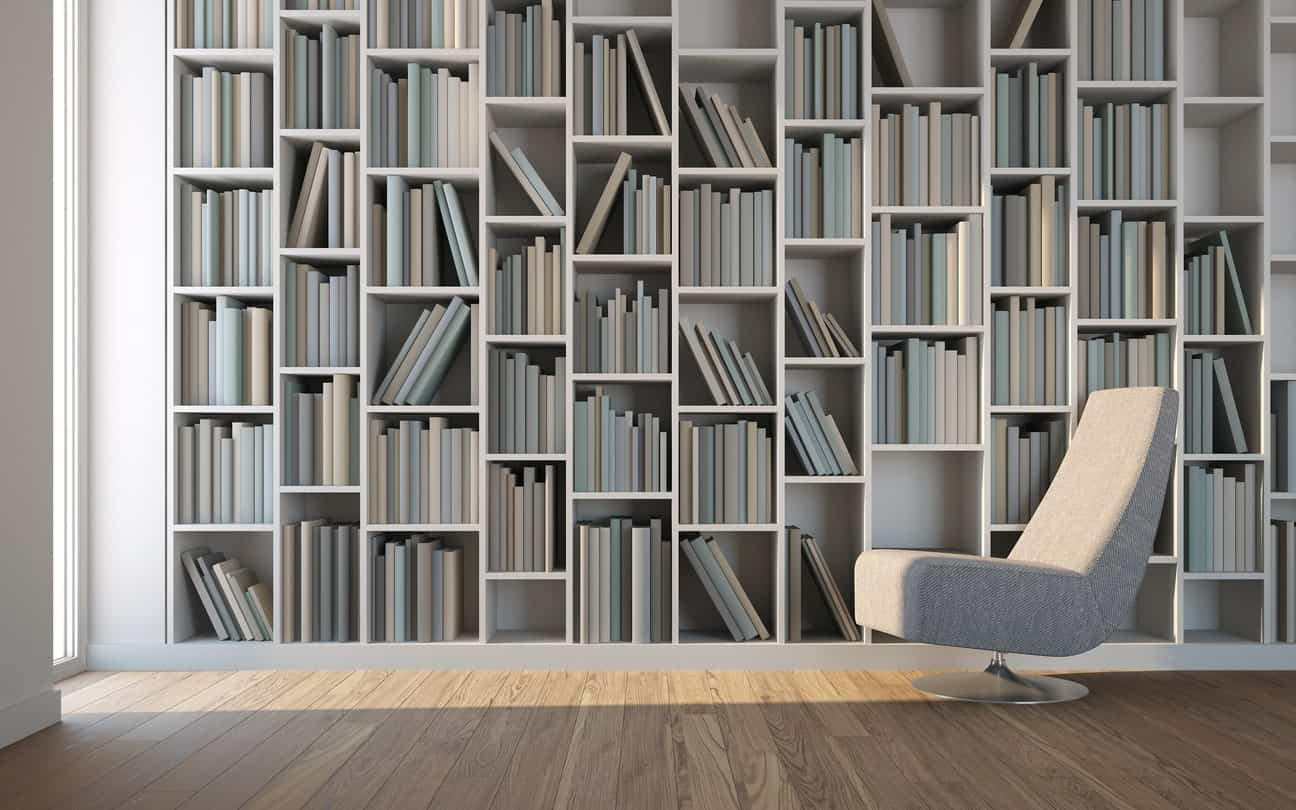 Sleek reading nook showcases a full height bookshelf and a modern gray chair over wood plank flooring.