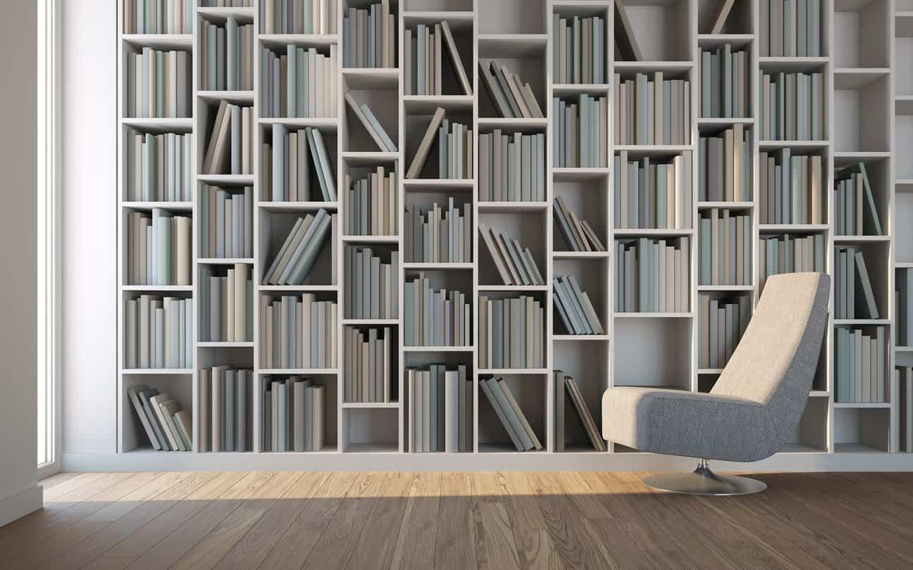 Sleek reading nook showcases a full height bookshelf and a modern gray chair over wood plank flooring.