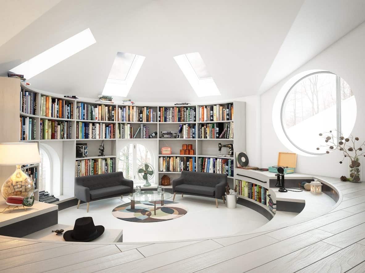 Round reading nook boasts a built-in bookshelf accompanied by gray sofas and glass top table that sits on a multi-colored round rug. It has arched and huge round windows along with skylights fitted on the white ceiling.