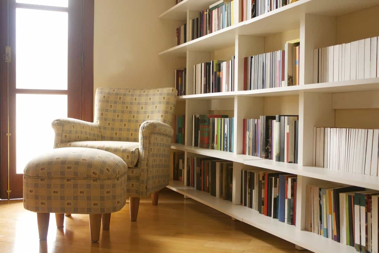 This reading nook offers a yellow patterned chair with matching ottoman over hardwood flooring.