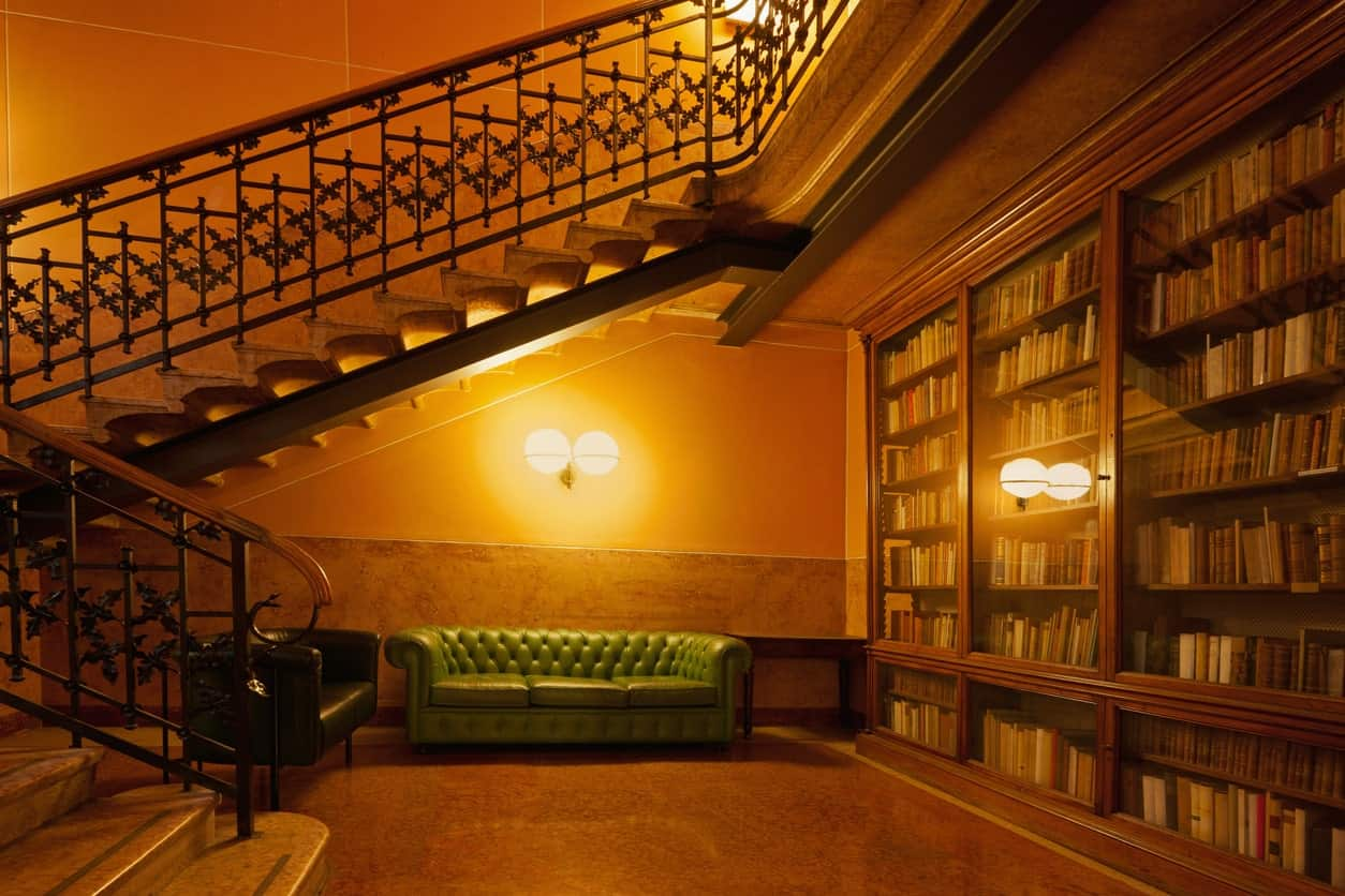Warm reading nook situated underneath an ornate staircase with green and black chesterfield sofas illuminated by wall sconces.