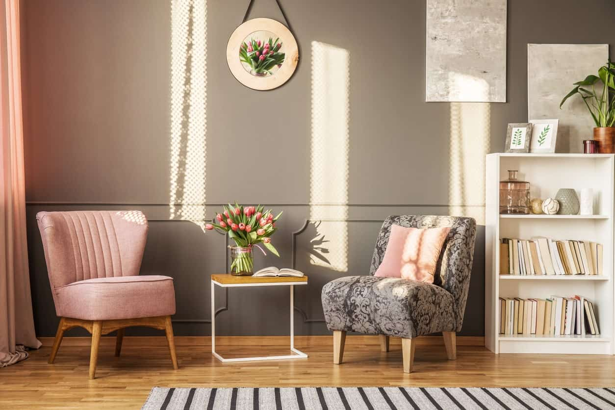 Charming reading nook furnished with pink wingback and black patterned chairs along with a wooden table in the middle. It has hardwood flooring topped with a gray striped rug.