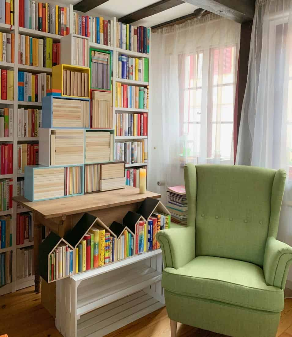 A green wingback chair sits in front of the glass windows covered with sheer curtains in this reading nook. It is paired with a natural wood table topped with multi-colored shelves that are filled with books.