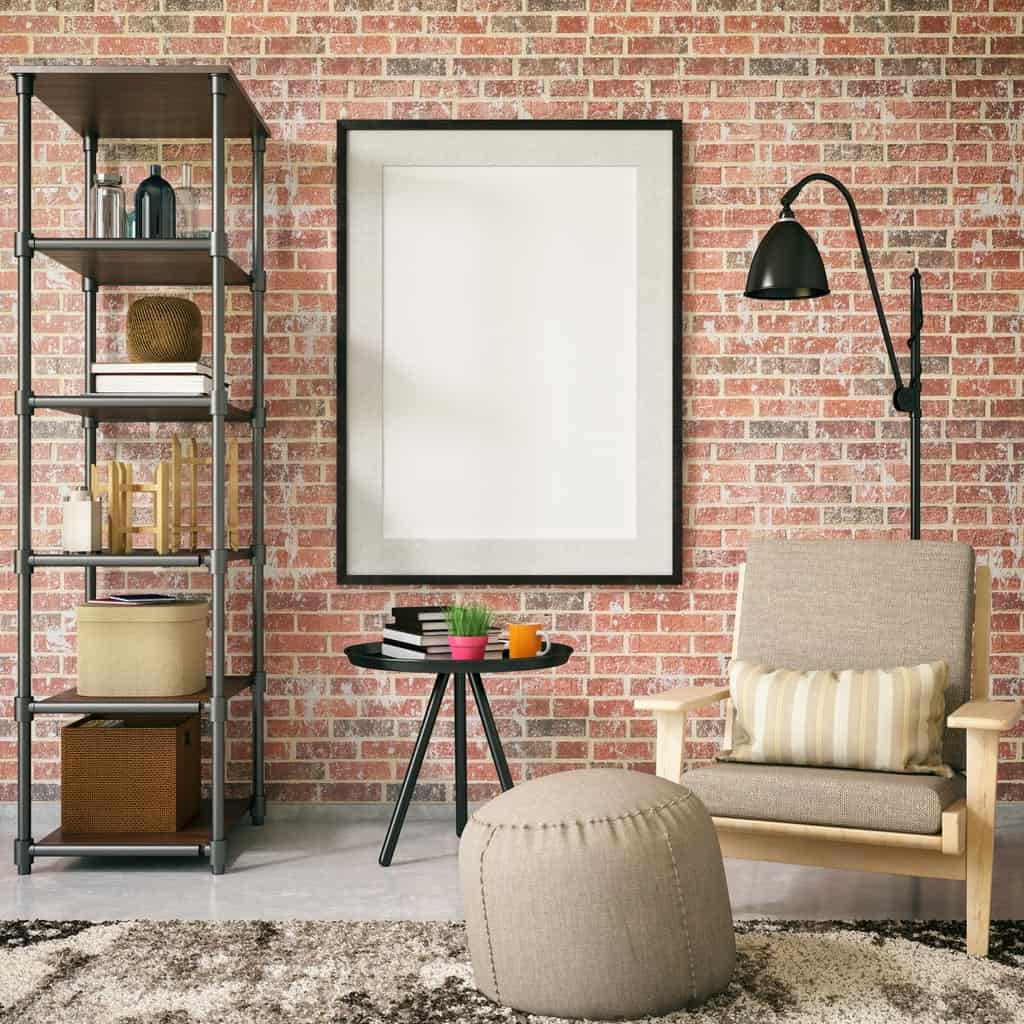 Industrial reading nook showcases polished concrete flooring and red brick wall mounted with a blank canvas. It has a brown chair paired with ottoman and black table along with a metal shelving unit.