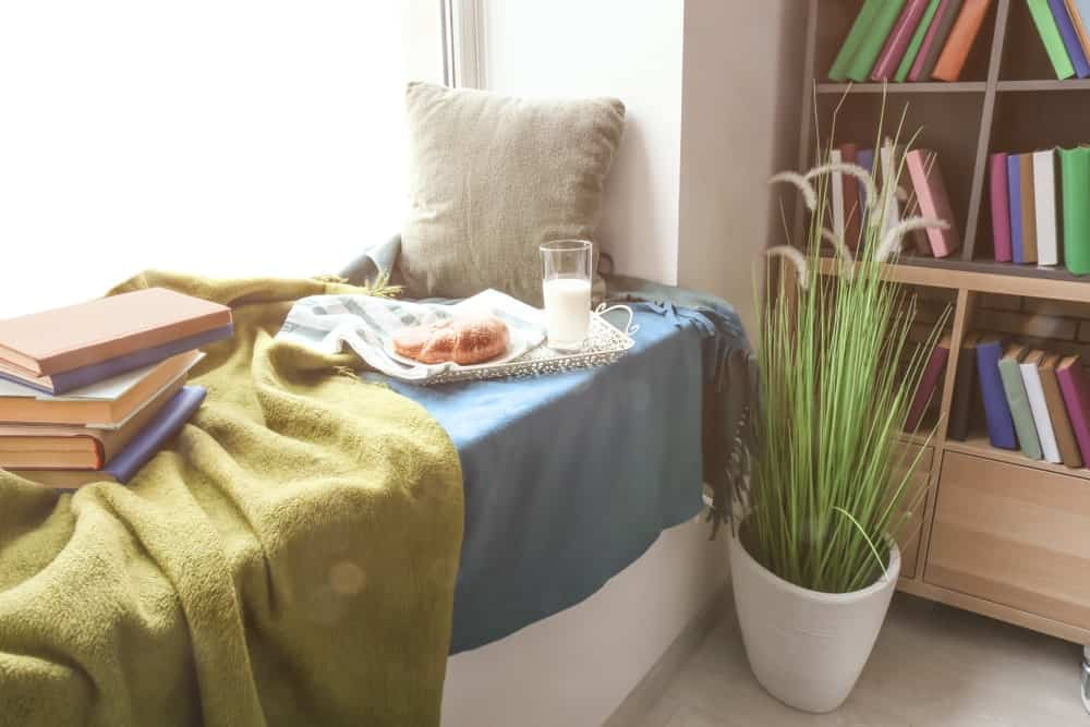 Window seat nook covered with green and blue blankets and accented with a potted plant. There's a wooden bookshelf adjacent to it over a light hardwood flooring.