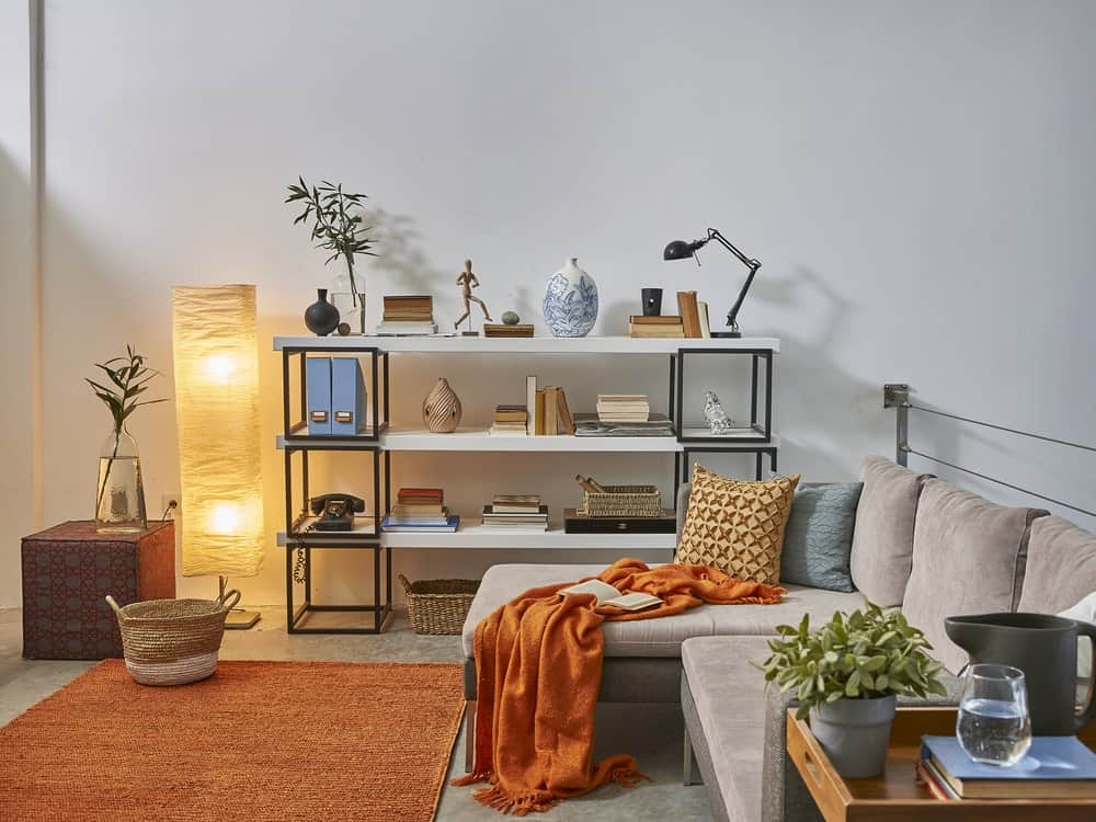 A fresh reading nook boasts a gray L-shaped sofa filled with pillows and an orange throw blanket that complements with the area rug.