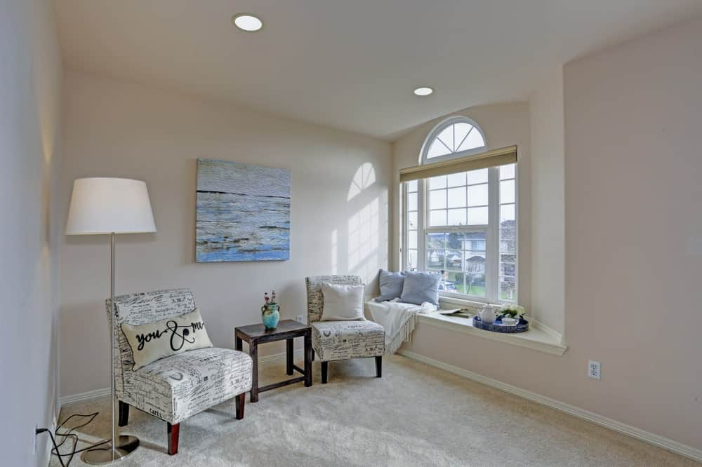 Spacious seat nook offers a pair of white chairs with a wooden table and lighted by a floor lamp along with natural light that flows through the window with built-in seat.