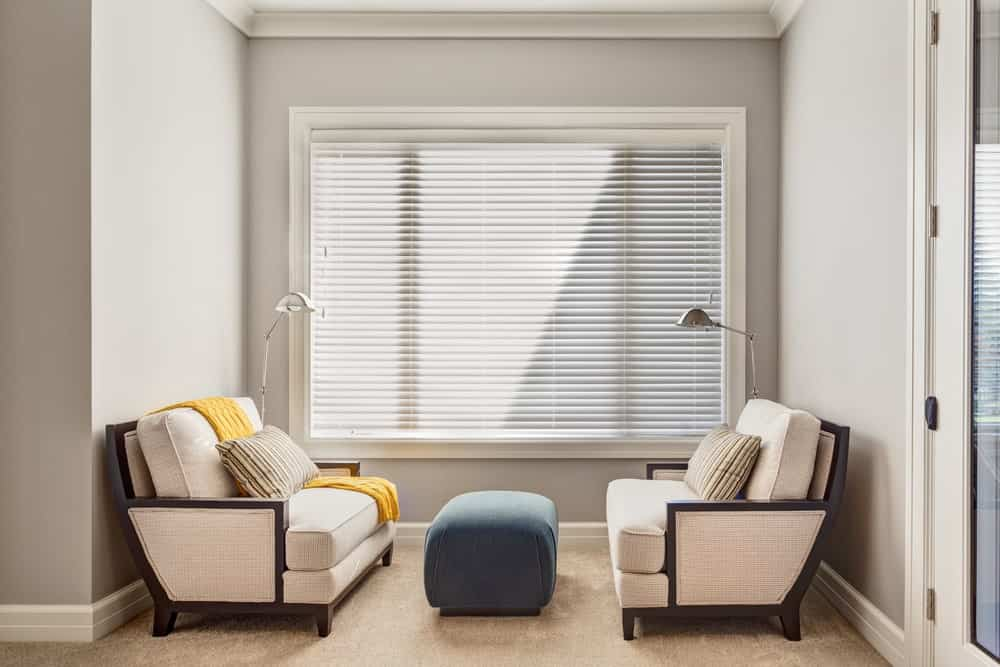 Sleek reading nook accented with a blue ottoman in between beige lounge chairs facing each other. It is situated beneath a picture window covered with white blinds.