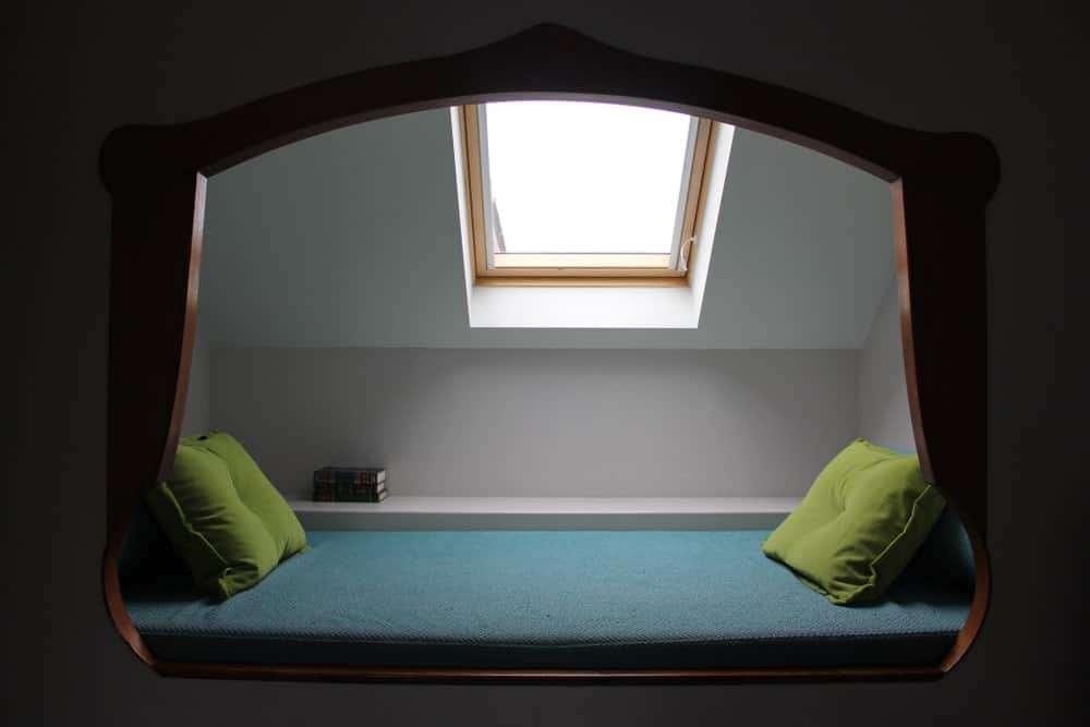 An alcove reading nook fitted with a teal cushion along with green throw pillows and illuminated by a skylight fixed on the white vaulted ceiling.