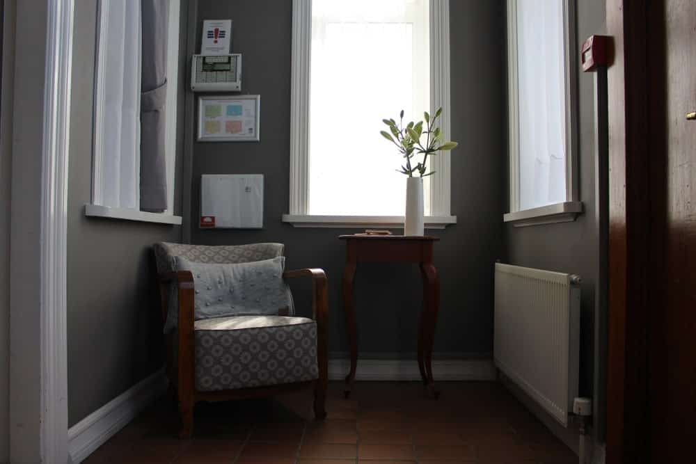 Dark reading nook surrounded with white windows fitted on the gray walls. It has a floral patterned chair and wooden side table accented with a fresh plant that gives life to the area.