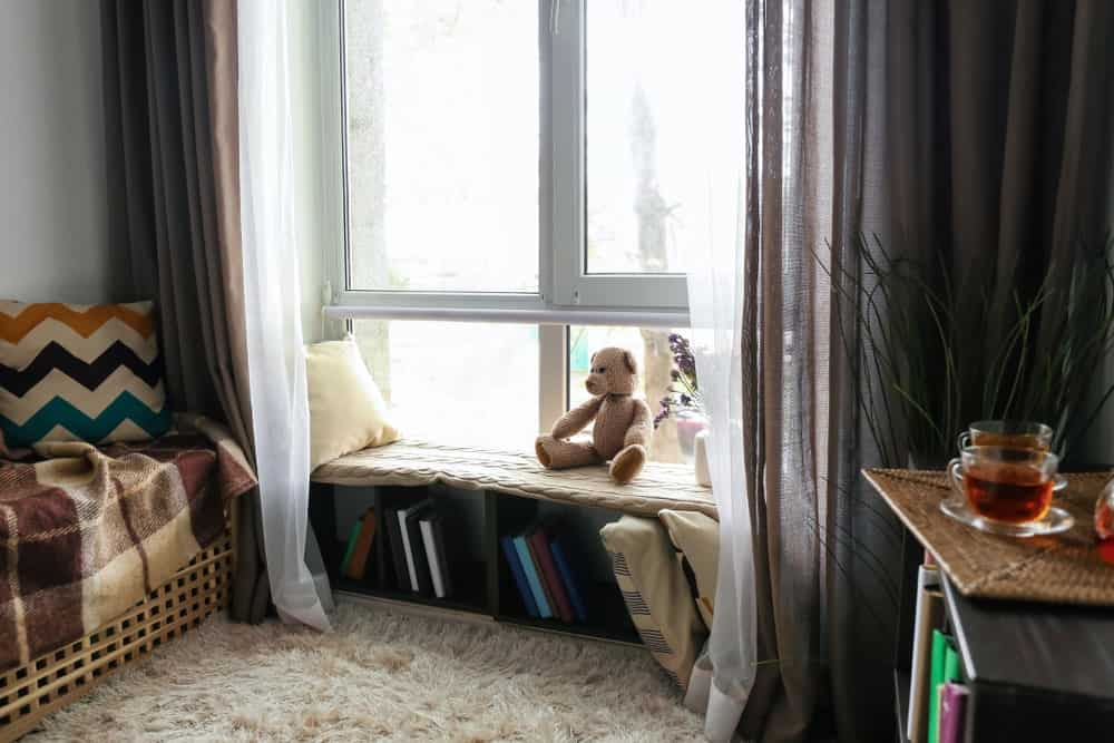 Airy window seat nook covered in brown and white sheer curtains. It is accented with a cute teddy bear and lavender plant.