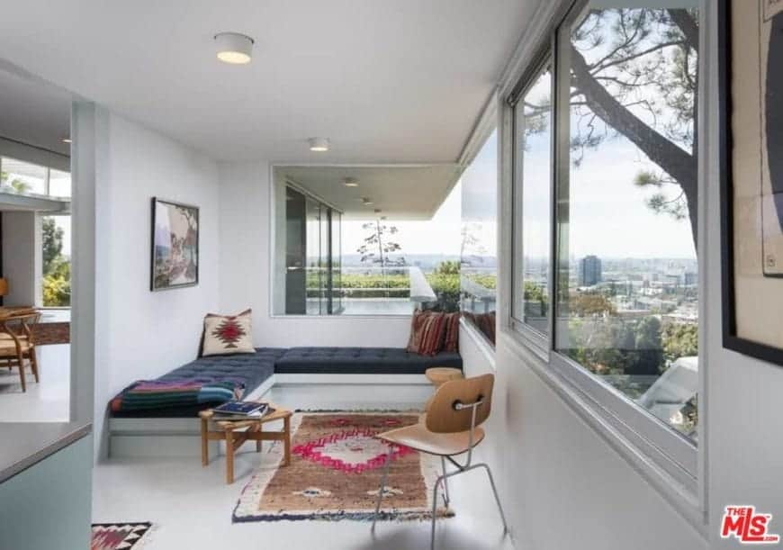 A gorgeous white reading nook decorated with a landscape wall art mounted above a deep blue L-shaped bench. It has a wooden chair and table that sit on white concrete flooring topped with a lovely rug.