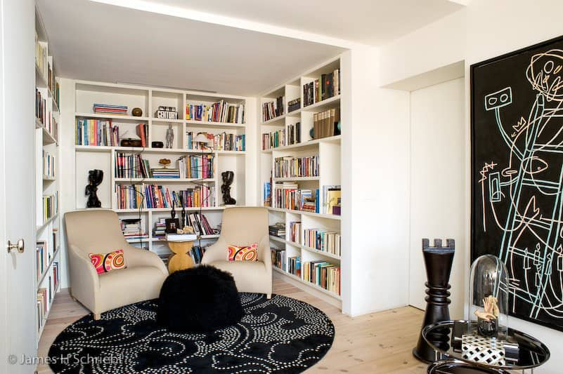 White reading nook beautifully contrasted with a black round rug and chalkboard decal. It has beige chairs and wooden side table surrounded by bookshelves.