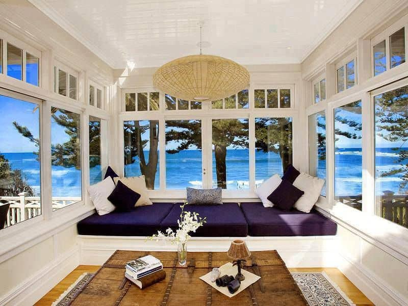 A wicker pendant lamp illuminates this reading nook along with natural light from the glazed windows with a stunning beach view. It has a window seat accented with violet cushions and neutral pillows.