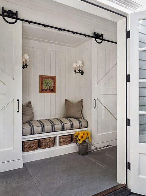 Reading nook fitted on the vertical shiplap walls illuminated by vintage sconces. It has open storage filled with rattan baskets and topped with a striped cushion.