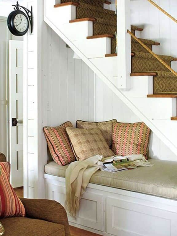This reading nook is fixed underneath a white staircase covered with moss green stair runner. It is filled with pillows and a beige throw blanket.