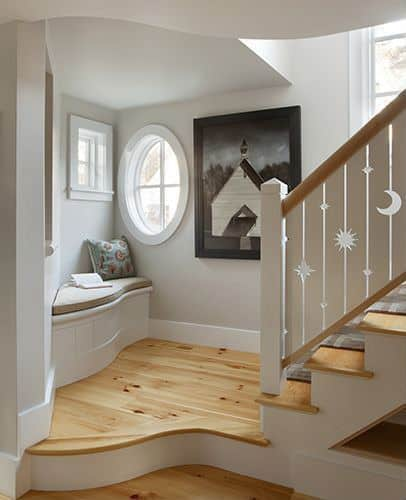 A charming reading nook placed in the corner of a wooden staircase landing. It is decorated with a lovely house wall mounted beside the round window.