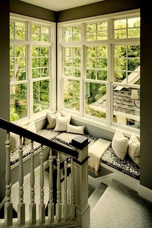 A reading nook by the window and staircase fitted with black patterned cushions that are topped with white fluffy pillows and throw blanket.
