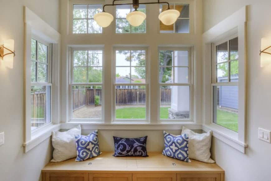 Warm pendant lights illuminate this reading nook along with sconces mounted on the beige walls. It has a wooden bench accented with white and blue pillows beneath the glass paneled windows.