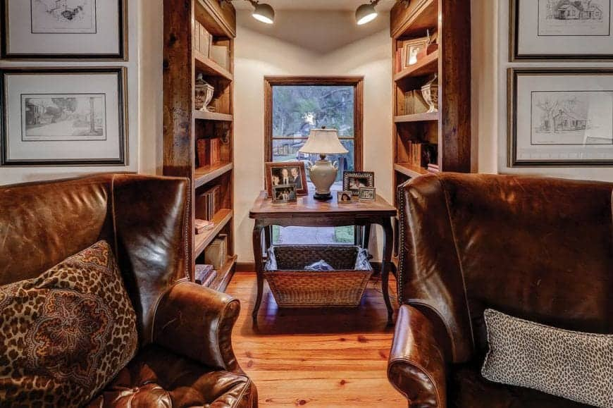 Warm reading nook offers leather wingback chairs and a wooden table topped with picture frames and desk lamp in between built-in bookshelves.
