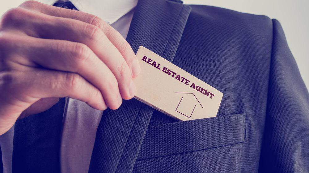 Hand holding a tag of a real estate agent and placing it on suit breastpocket.