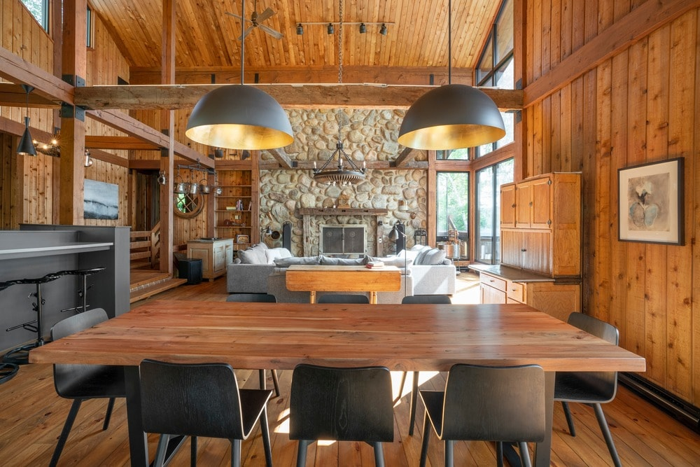 Large rustic great room featuring a gorgeous living space with a large stone fireplace along with a dining area with a wooden rectangular dining table set lighted by pendant lights.