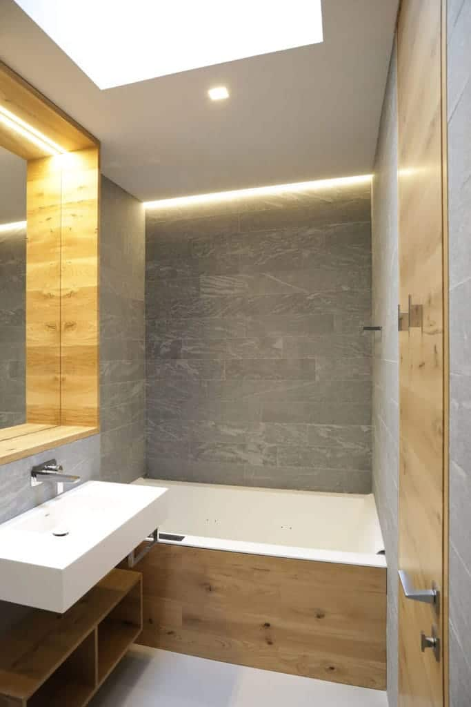 This small and simple bathroom has a few modern elements combined to its Rustic-style aesthetic. The white bathroom is inlaid with the same wooden material as the floating shelf beneath the white sink and the frame of the vanity mirror.