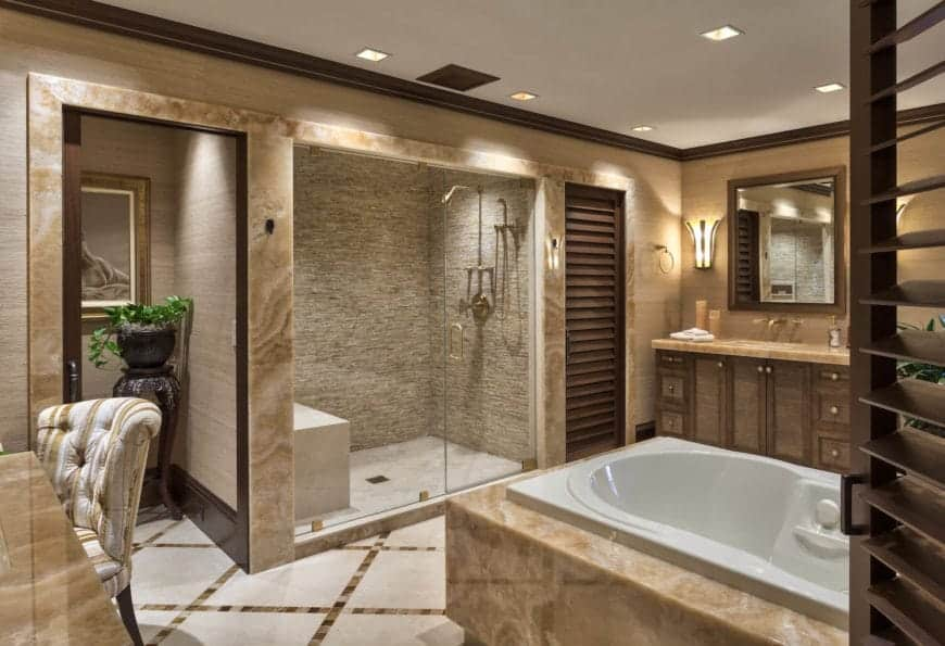 This elegant and luxurious bathroom has a beige wallpaper that makes it look like wood. This pairs well with the beige marble that accents the walls and countertop of the vanity as well as the inlay of the white bathtub illuminated by the recessed lights of the ceiling.