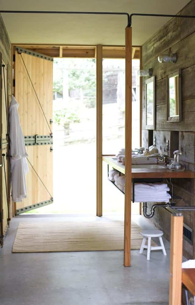 This charming bathroom is a combination of the Rustic-style and the Farmhouse-style. It has large wooden doors that look like barn doors leading to a floating vanity with a wood countertop against the wooden wall that goes well with the gray concrete floor.