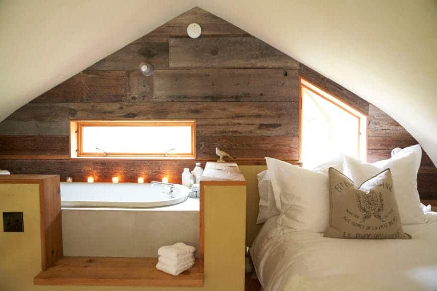 This is a relatively small bathroom that is directly beside the bed separated only by a small wood and beige enclosure that matches with the wooden wall with a small slit-like window over the white bathtub at the corner under a low white cathedral ceiling.