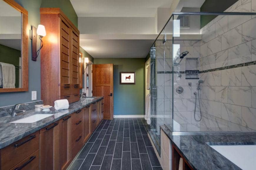 The beautiful dark gray tiles of the floor pairs well with the gray walls that complement the wooden cabinetry of the two-sink vanity. This has gray marble countertops that matches with the white marble walls of the glass-enclosed shower area.