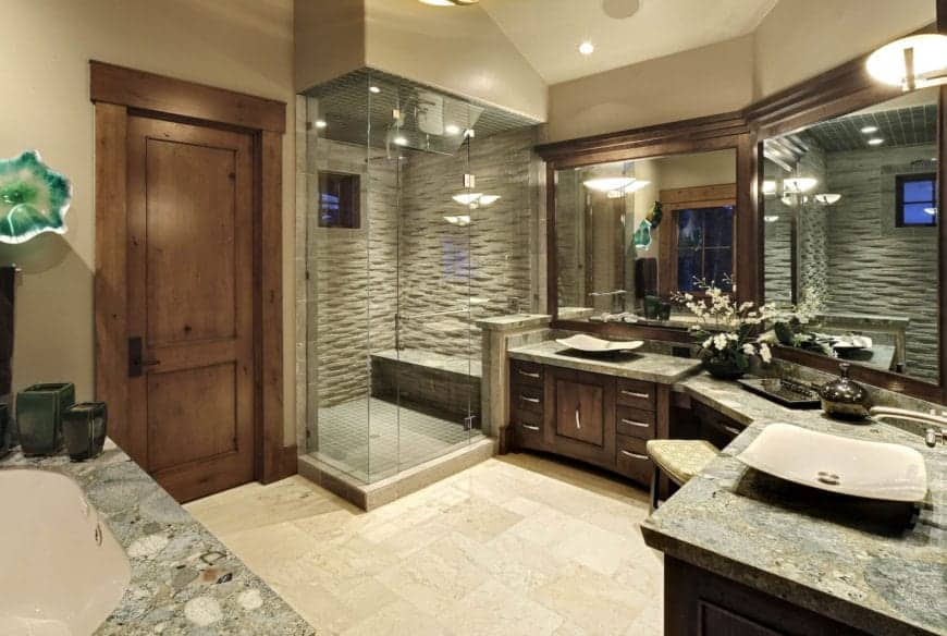 This bathroom has a beige marble floor that complements the dark wooden cabinets and drawers of the vanity. This is topped with gray marble countertops an large vanity mirrors with wood frames similar to the cabinets. This setup leads to the glass-enclosed shower area that has textured wall