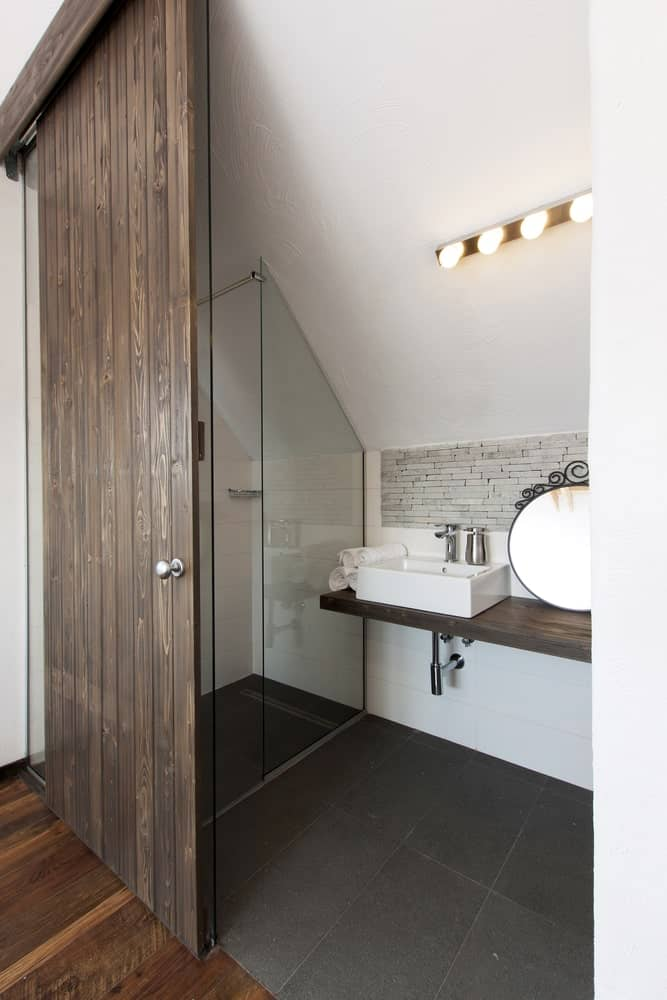 This is a small Rustic-style bathroom with a beautiful wooden sliding door leading to the gray tiles of the floor that is contrasted by the white shed ceiling and white walls beside the floating wooden sink is the glass enclosed shower area.