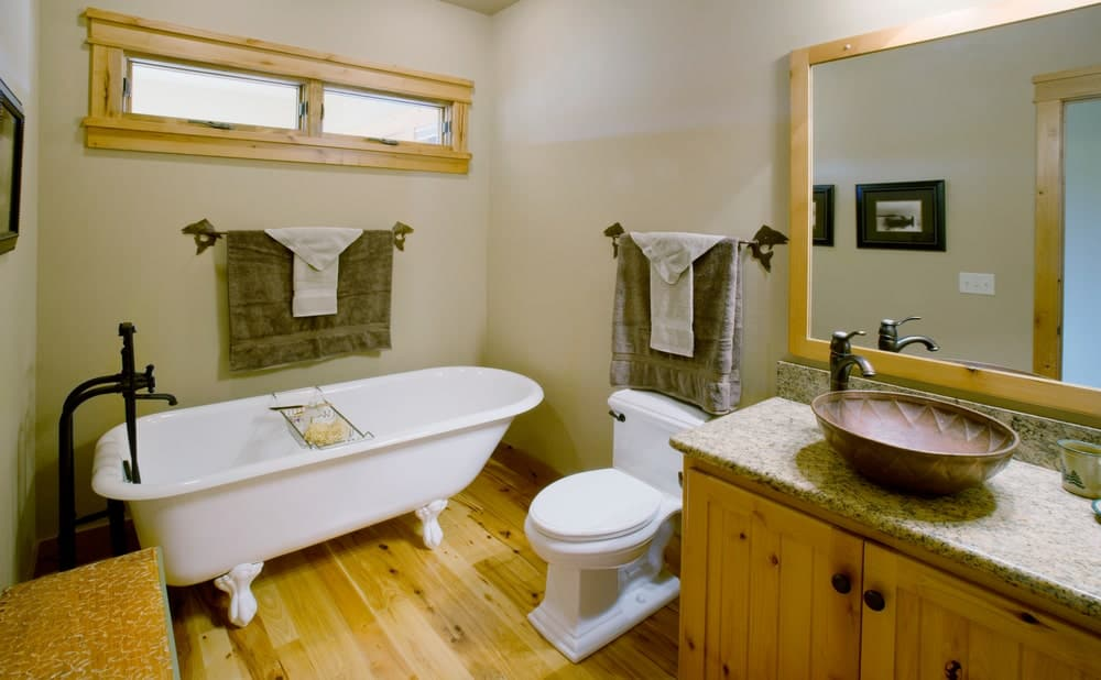 The white freestanding bathtub with white legs is topped with a narrow slit-like window with wooden frames that match the frame of the vanity mirror, the cabinets of the vanity as well as the hardwood flooring that complements the toilet and tub.