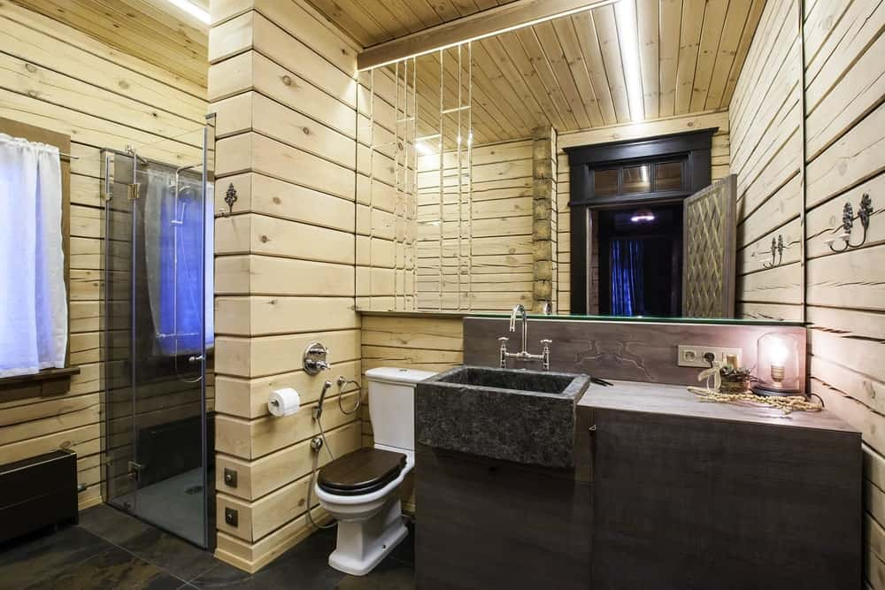 This charming bathroom has light wooden planks on the walls arranged in a shiplap pattern. This contrasts the dark stone vanity and its stone basin sink as well as that dark brown lid of the toilet. The large mirror above the toilet and vanity matches the glass door of the shower area.