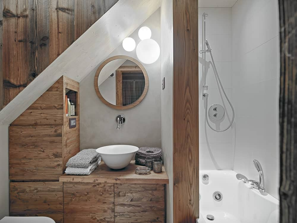 This is a small Rustic-style bathroom right under the stairs that is why it has a wooden vanity that follows the lay of the stairs. This wooden vanity is paired with a white porcelain bowl that matches with the bathtub beside the vanity.