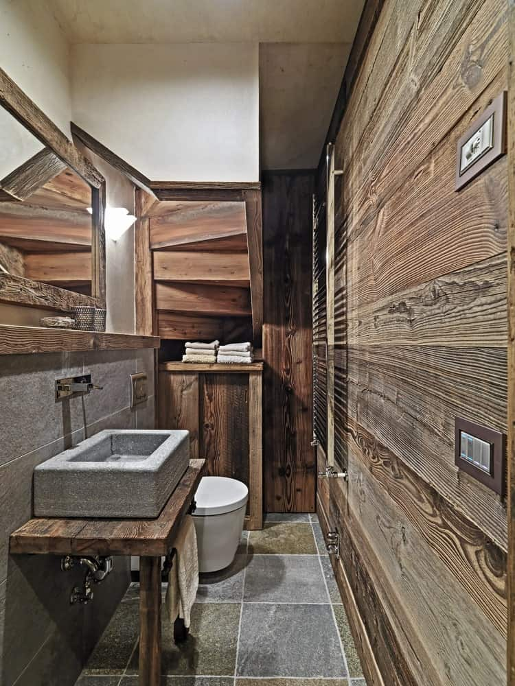This is a Rustic-style bathroom that has a small floor space underneath a staircase. This is evident on the wooden ceiling above the white toilet that has makes of steps that matches the wooden wall that is complemeted by the gray stone tiles of the floor.