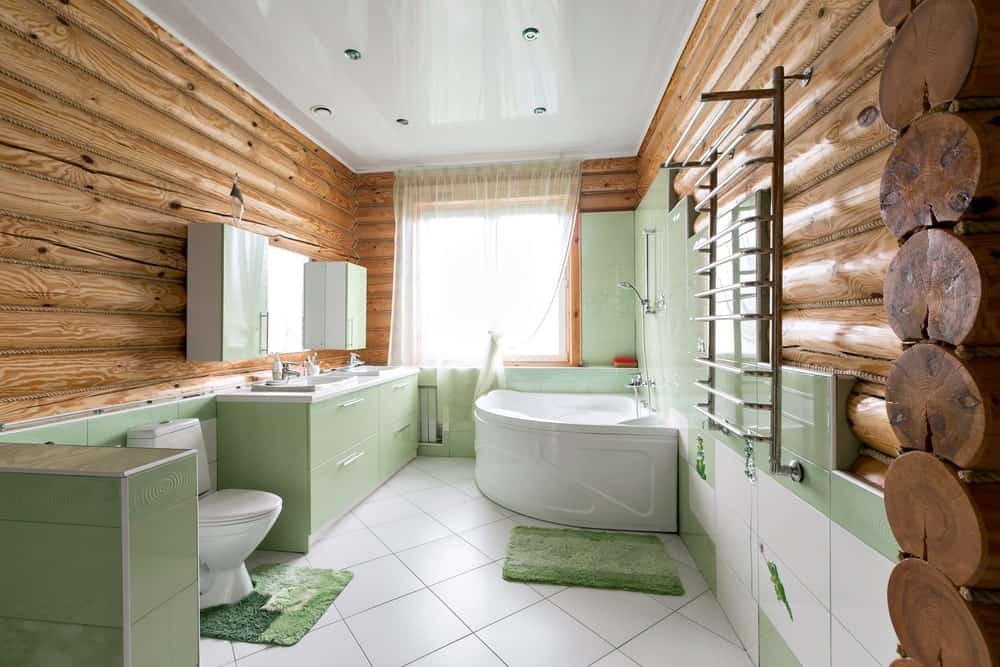 The wooden log cabin walls of this Rustic-style bathroom sets a lovely complement to the green tone of the lower half of the bathroom. There are green tiles, green vanity and green area rugs the adorn the white tiles of the floor.