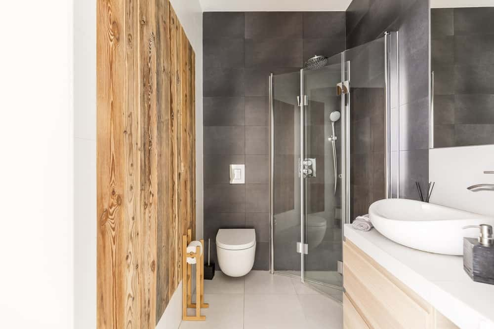 The glass-enclosed shower area is placed in a corner of dark gray wall tiles beside the white floating toilet. Adjacent to this toilet is a wall that is dominated by wooden planks that complement the light wooden hue of the vanity that has a white countertop.