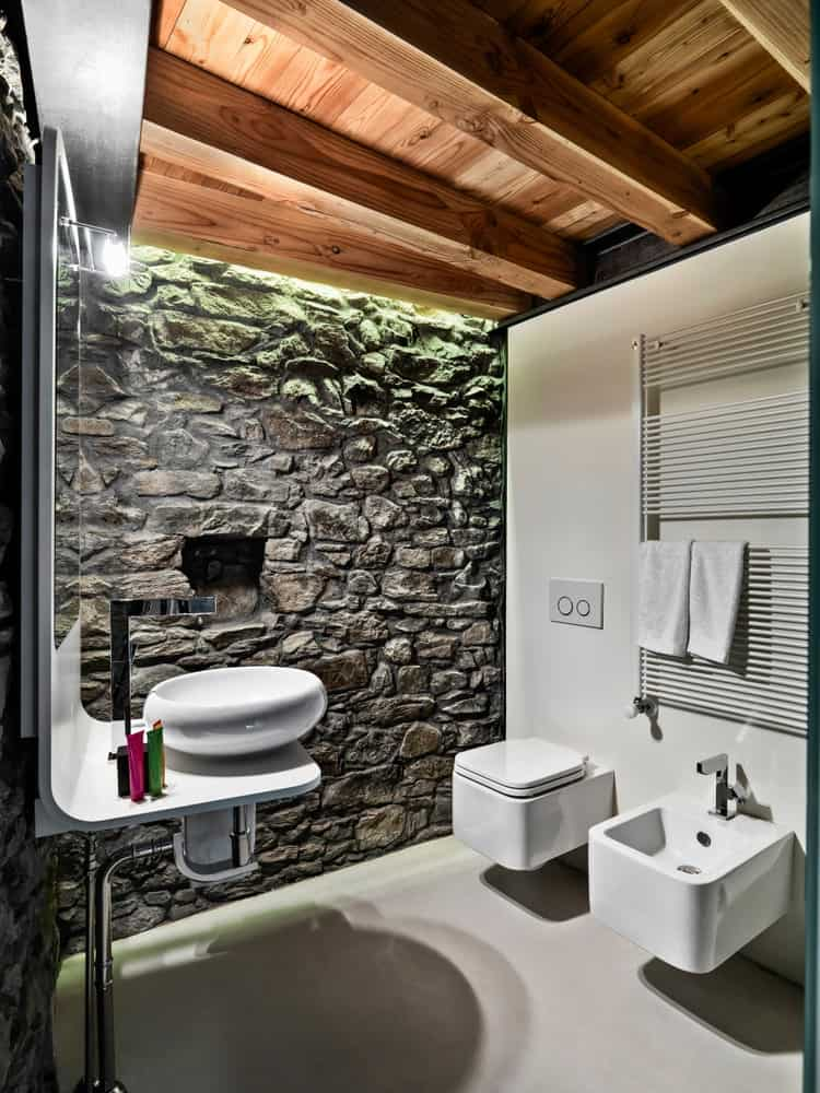 The far wall of this Rustic-style bathroom is textured and made of stone as well as the stone wall adjacent to it. These are all complemented by the wooden ceiling with exposed wooden beams and the white floor that matches with the toilet and sink.