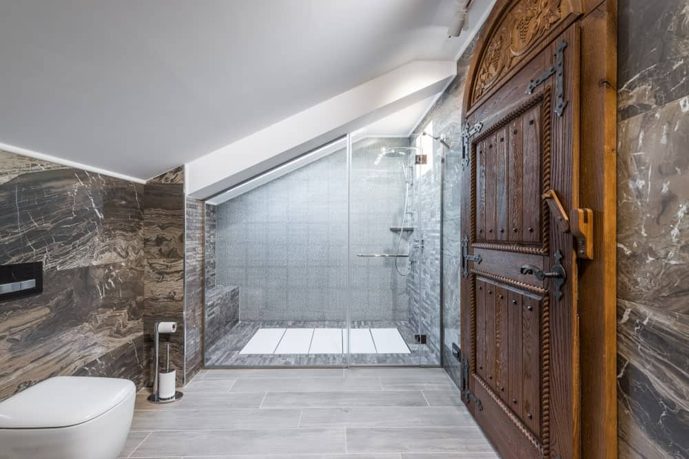 The simple aesthetic of this bathroom is elevated to a Rustic-style bathroom with the addition of the Rustic wooden door that has a wooden locking system, iron studs and an intricate carving on its top. This is contrasted by the white ceiling and light hardwood flooring.