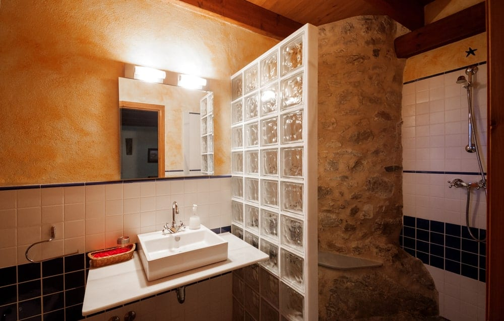The shower area is separated from the rest of the bathroom by a frosted glass wall with white frames matching the white floating vanity of the white porcelain basin of the sink. The shower area is dominated by a large stone textured structure with a built-in seat.