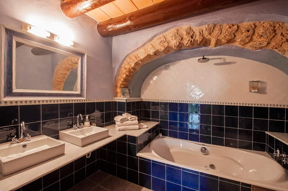 The lower part of the walls are filled with bright blue tiles that contrast the white sinks as well as the white bathtub that has the same silver fixtures as the floating vanity. These are then topped with a wooden ceiling that has exposed wooden log beams.