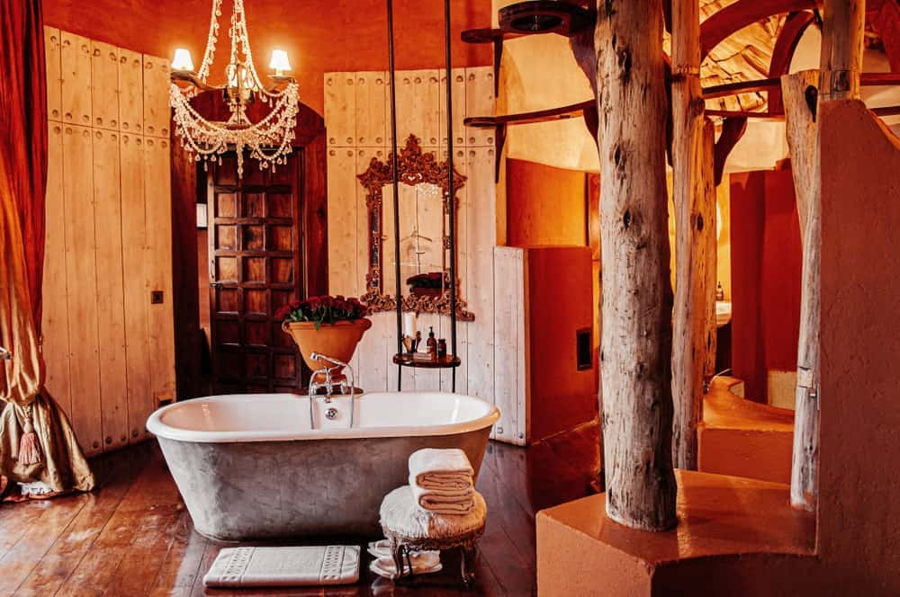 Those beautiful rough log columns are complemented by the terracotta base and the hardwood flooring that is contrasted by the light hue of the wooden walls as well as the freestanding porcelain bathtub that has a light gray hue on its outside.
