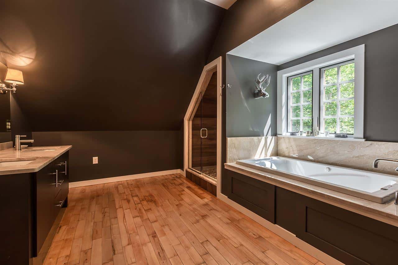 The large white porcelain bathtub is placed by the French windows. This is adorned with a decorative silver sculpture of a moose head mounted on the gray wall by the head of the tub. Beside the tub is the glass door of the shower area that has wood-like tiles on its walls.